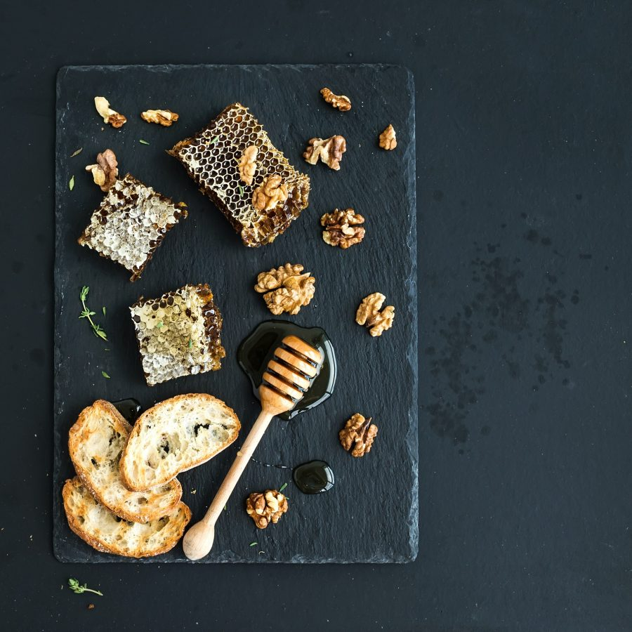 Honeycomb, walnuts, bread slices and honey dipper
